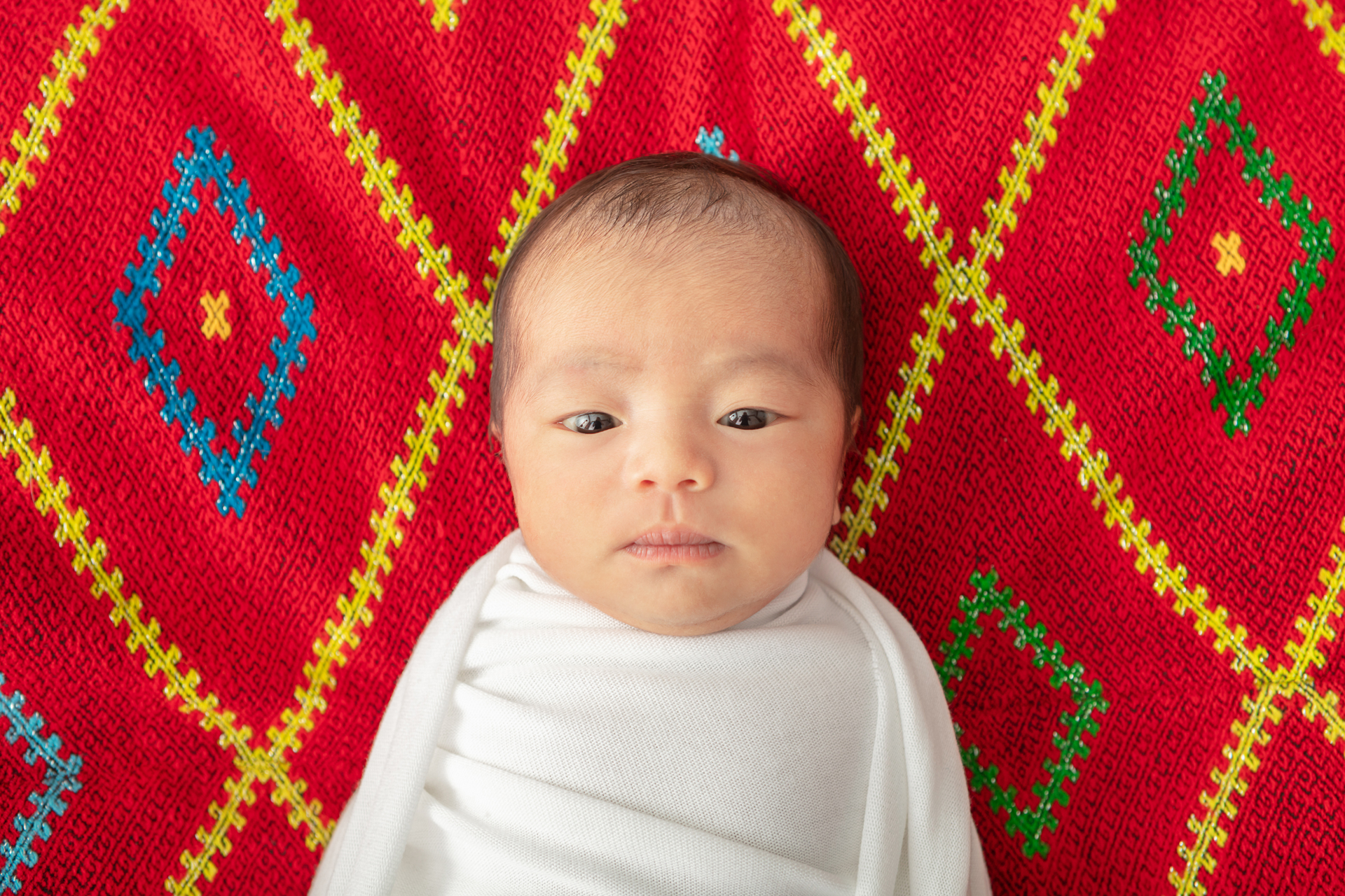 newborn baby girl looking at the camera; she is wrapped in a smooth white swaddle and has a traditional Asian garment behind her; red and blue and yellow and green diamond pattern