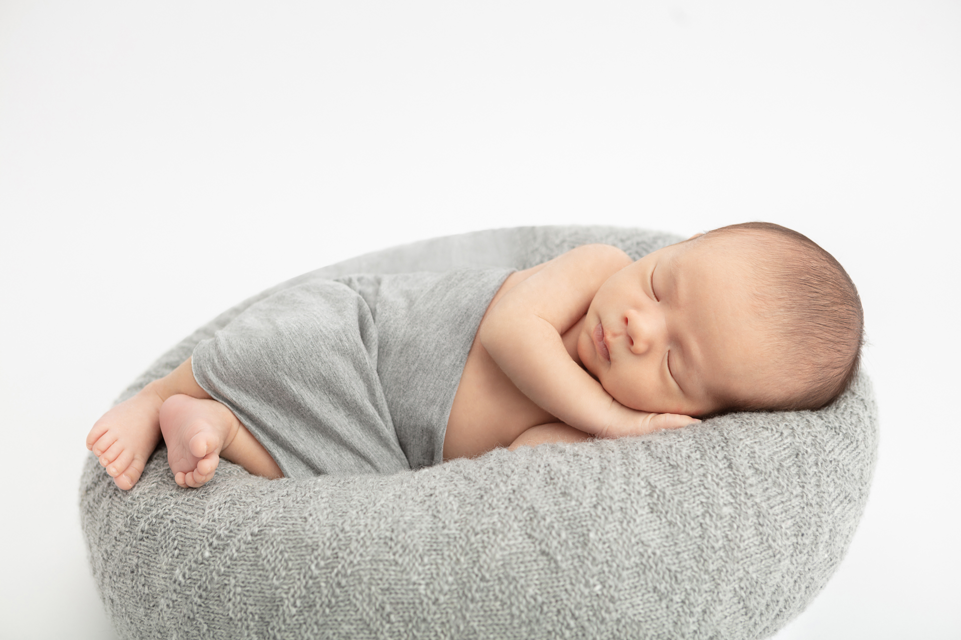 newborn baby boy wrapped in a gray heather swaddle and lying on a gray knit pouf