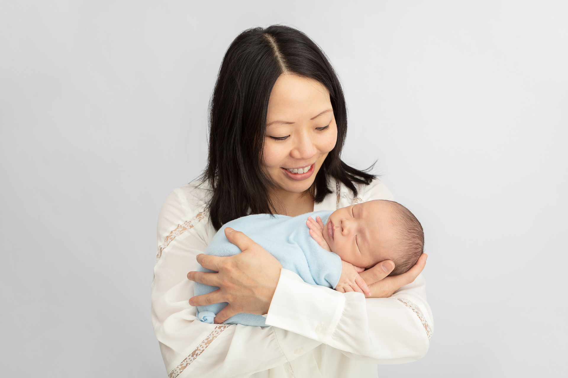 happy new mom holding her newborn baby in her arms, who is swaddled in blue