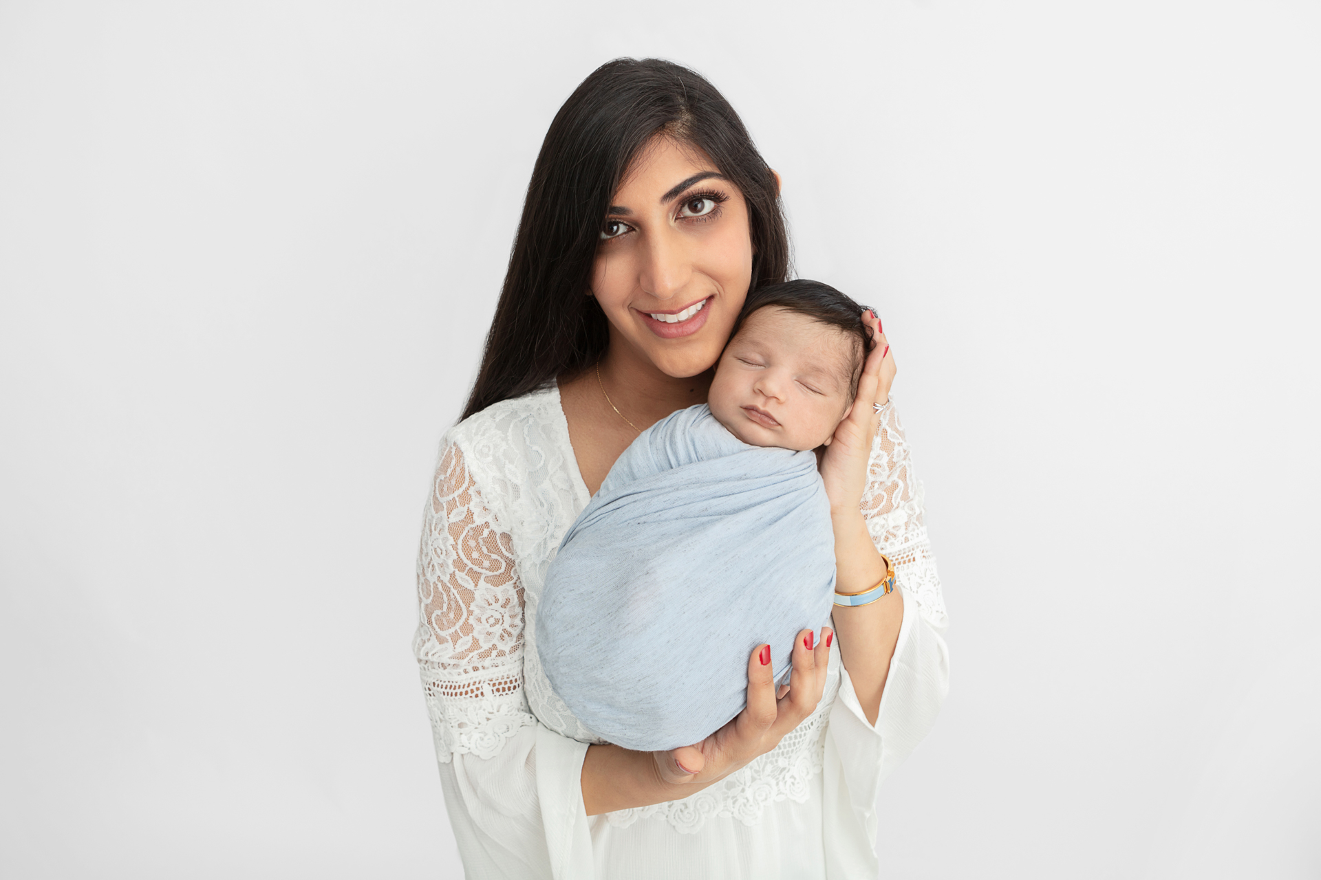 new mom with long dark hair and a white lace dress, holding her son who is swaddled in light blue