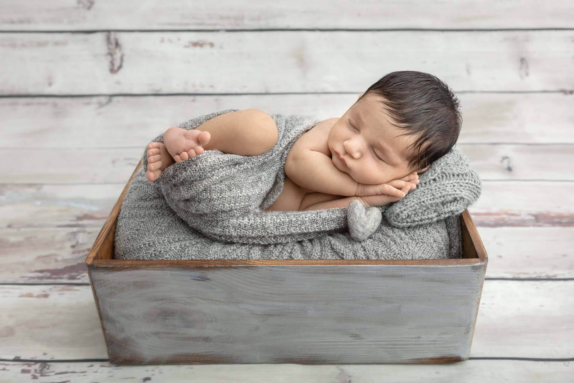 rustic newborn baby image with barn wood paneling backdrop; gray rustic box; gray heather swaddle
