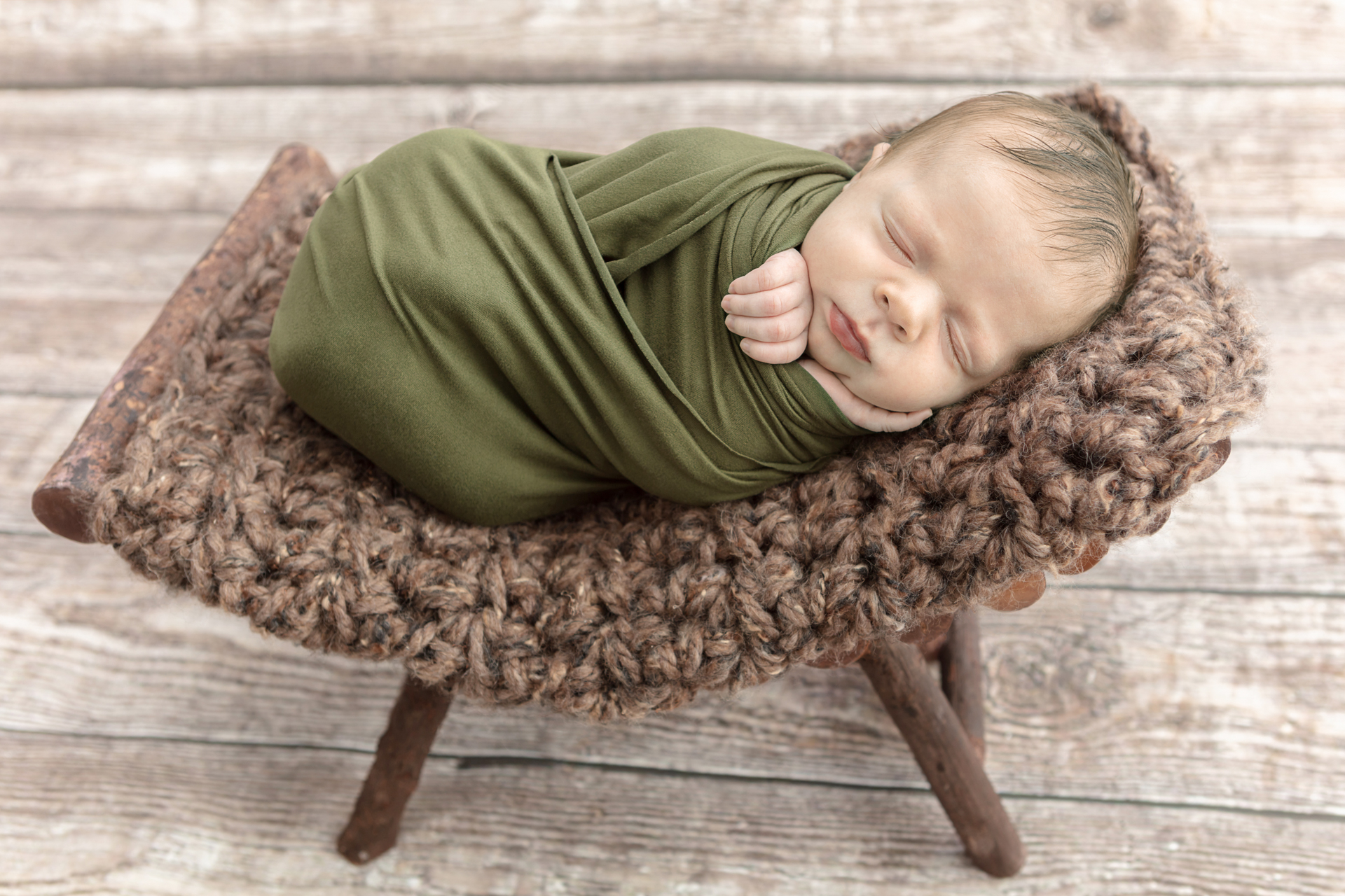 newborn baby boy wrapped in a moss green swaddle with one hand holding onto the front of the swaddle