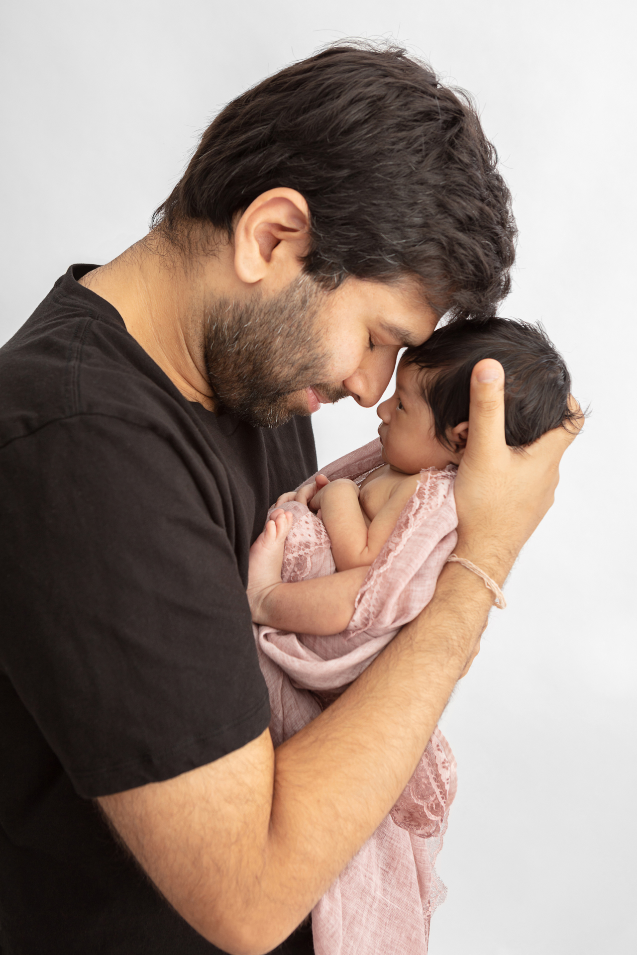new father leaning his head down to touch foreheads with his newborn baby girl who has her eyes open