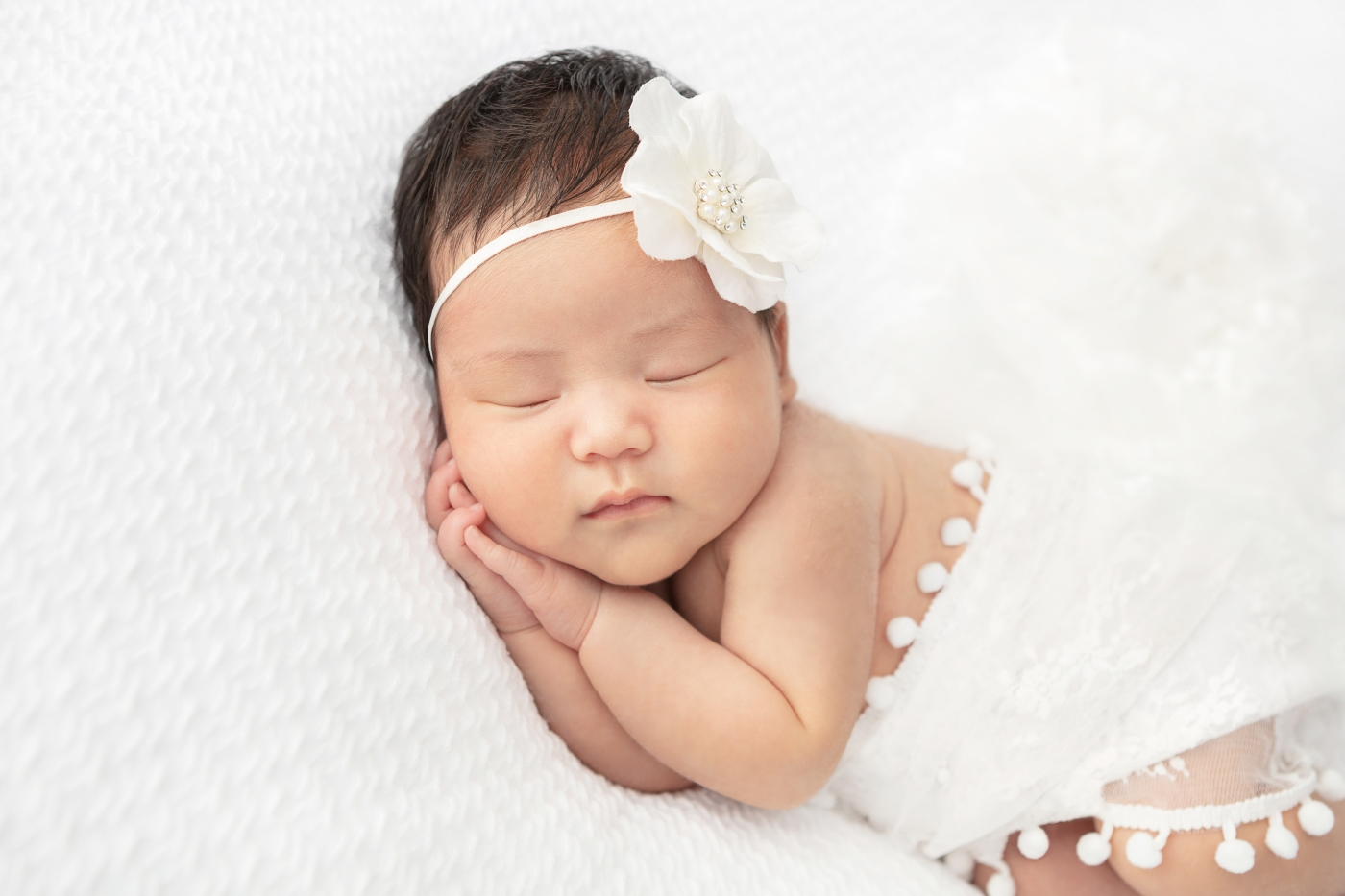 newborn baby girl with dark hair wrapped in a white lace fabric cradled on a soft white fabric withy a white flower headband, hands clasped under her cheek in a sleepy pose