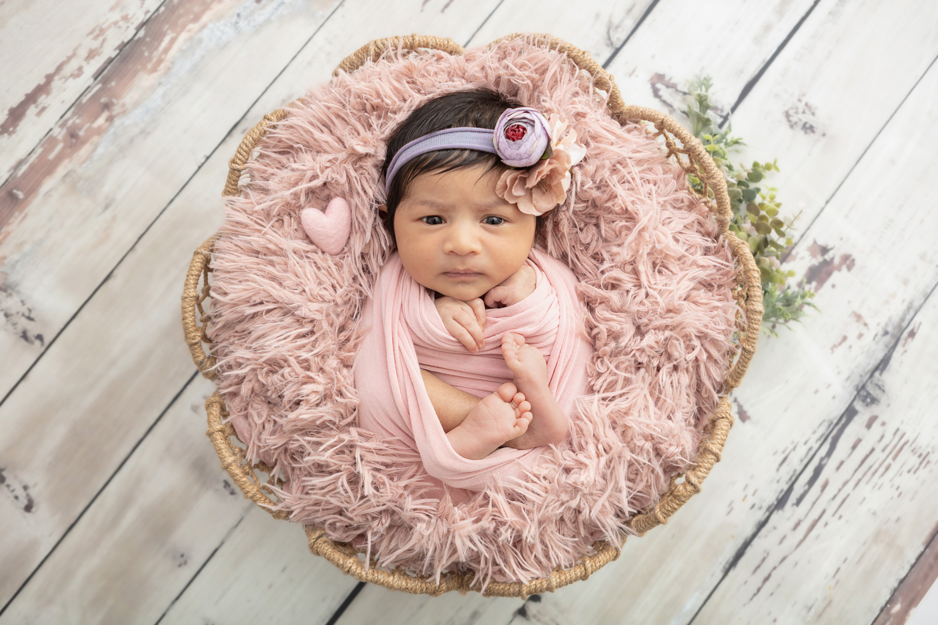 newborn baby girl with a lot of dark hair, wrapped in dusty pink with a felted pink heart