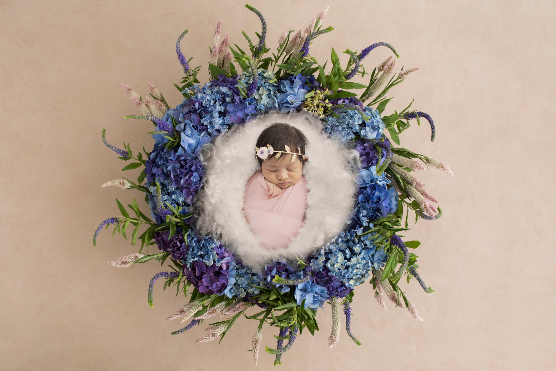 newborn baby girl wrapped in light pink and wearing a delicate headband; white fluff in a basket; floral newborn image