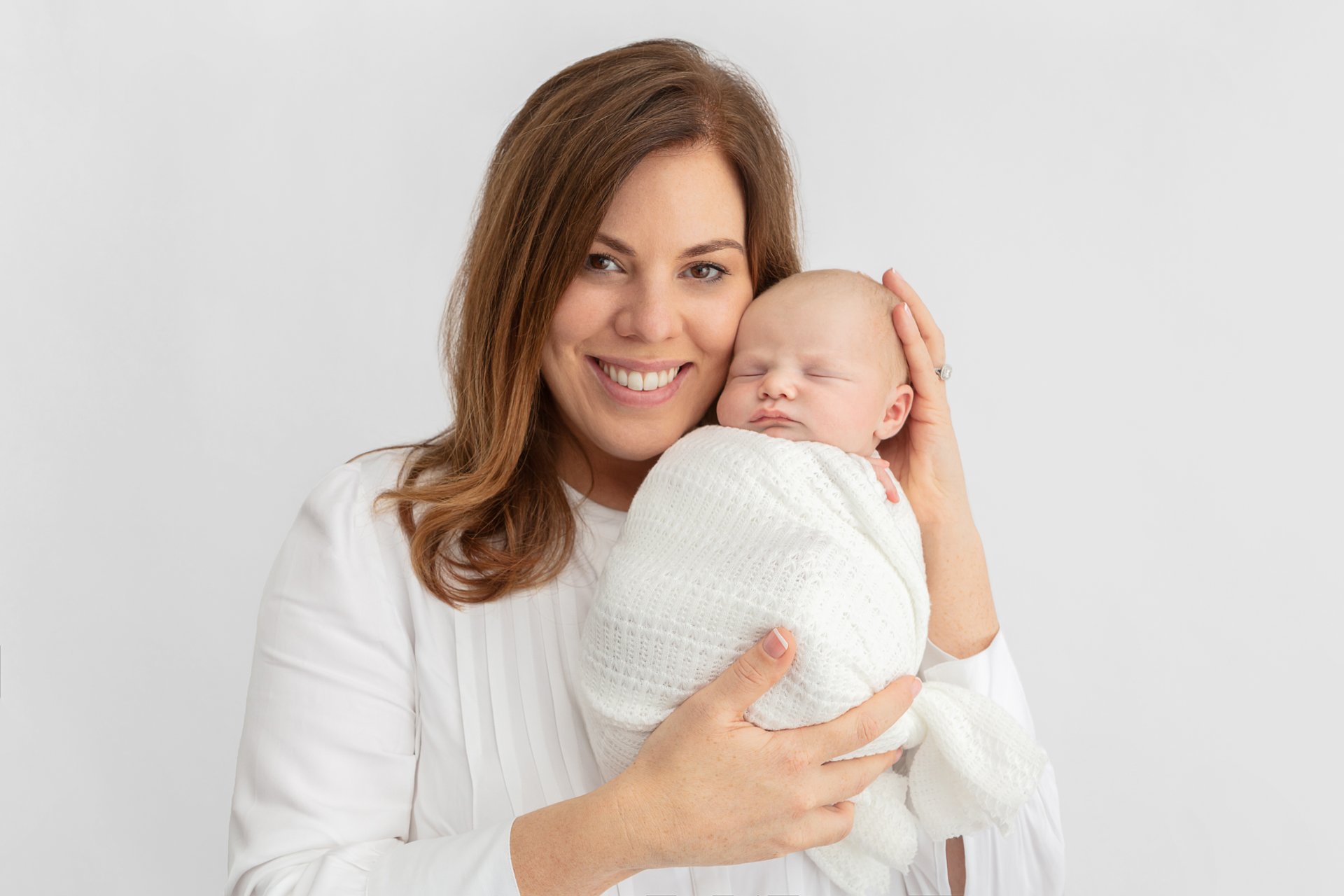 smiling Irish mom holding her newborn son against her cheek; mother and baby are in white