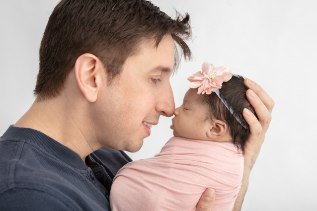new dad touching noses with his newborn baby girl who is swaddled in pink and wearing a large pink flower headband