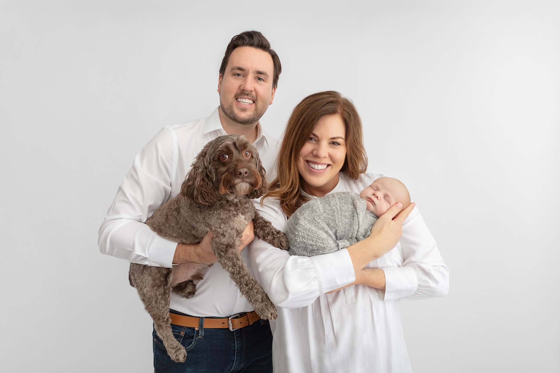 smiling new family of four; cockapoo, dad, mom, and baby boy; newborn family portrait with dog