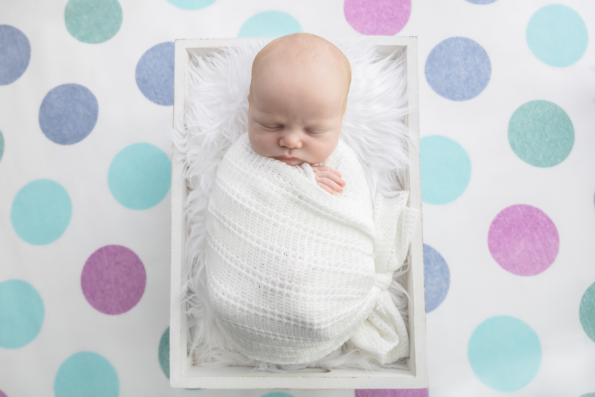 blue, aqua, soft green, and soft purple polka dot background; newborn baby wrapped in an open knit white swaddle