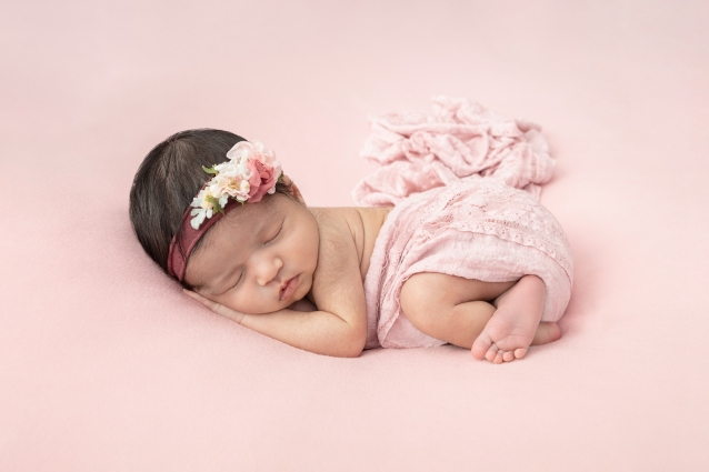baby girl asleep on a pink backdrop and wrapped in a pink swaddle while wearing a floral headband