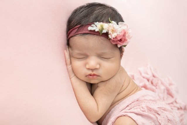 newborn baby girl with a lot of dark hair asleep against a pink pillow and wearing a pink floral headband