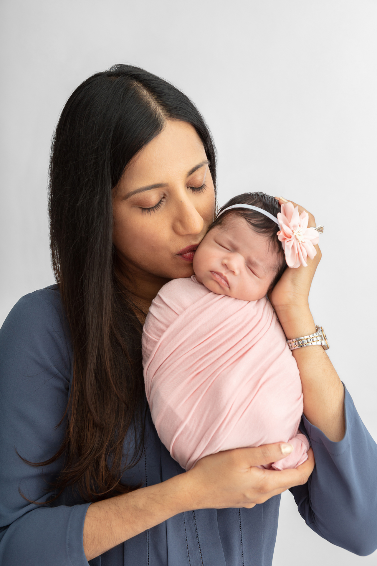 new mom with long dark hair holding up her newborn baby girl who is swaddled in light pink