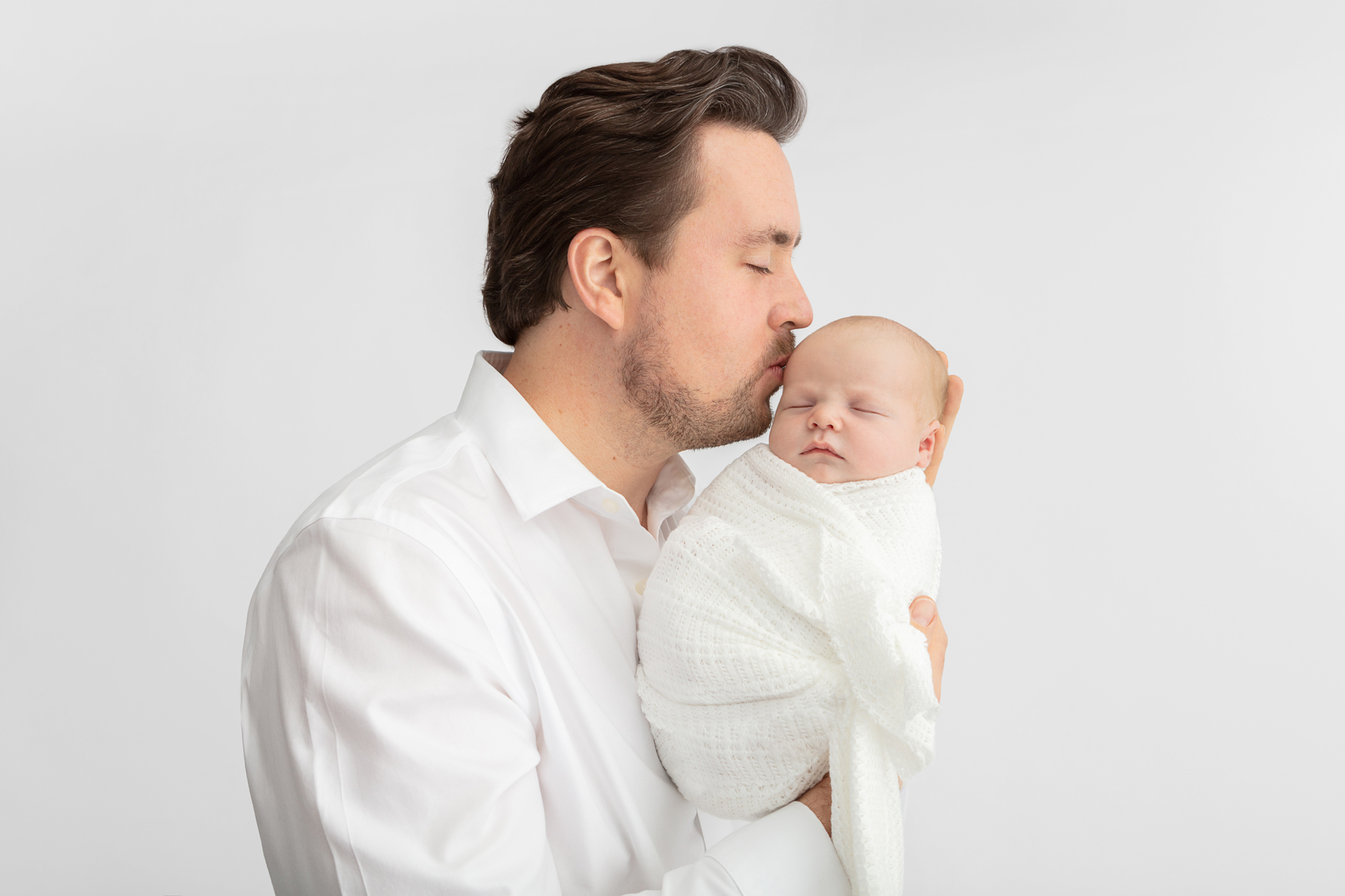 new dad in white shirt holding his son up and kissing his head; baby boy wrapped in white