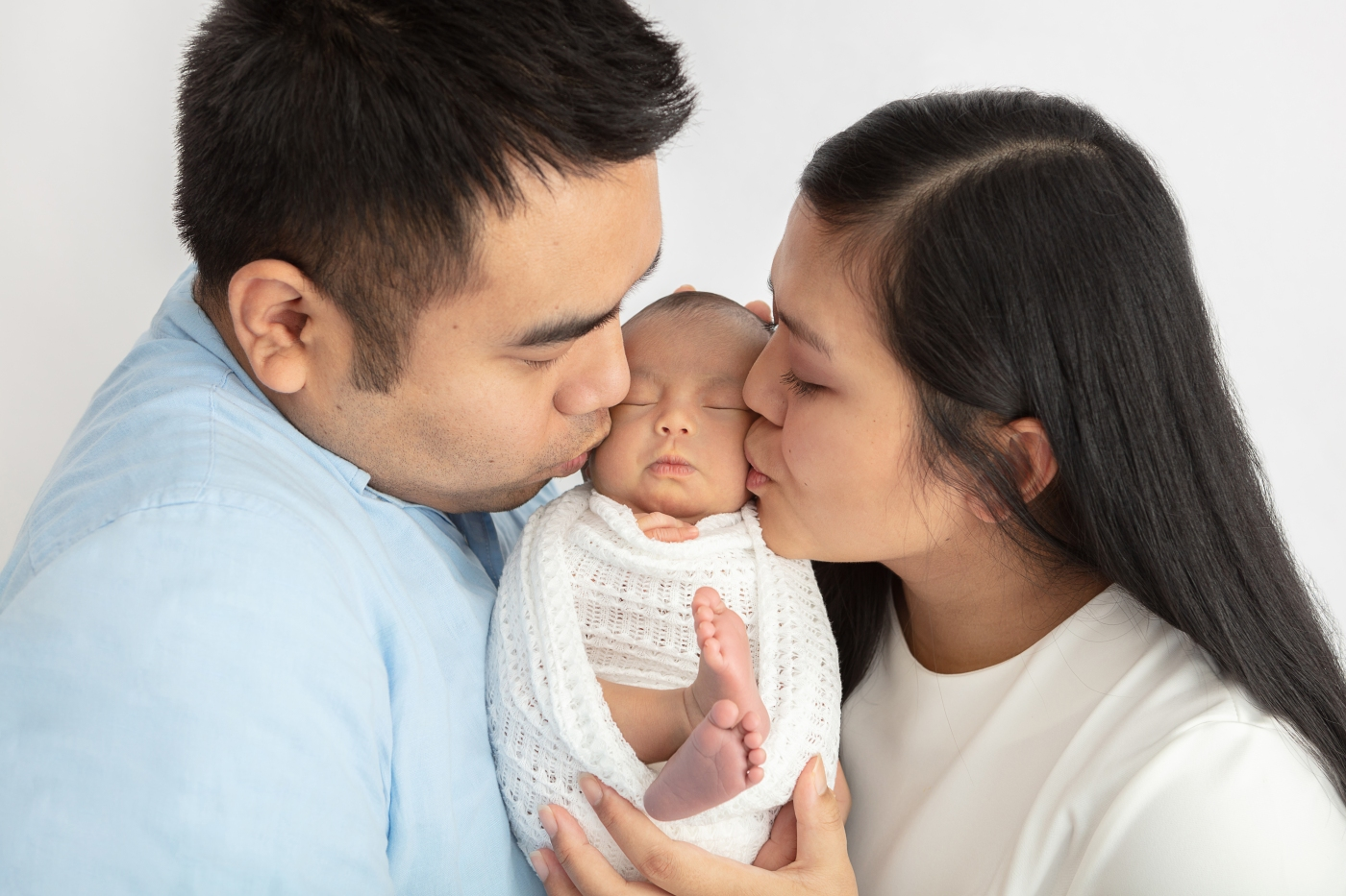 newborn baby wrapped in textured white fabric nestled between mom and dad both kissing baby's cheeks in a loving new family scene
