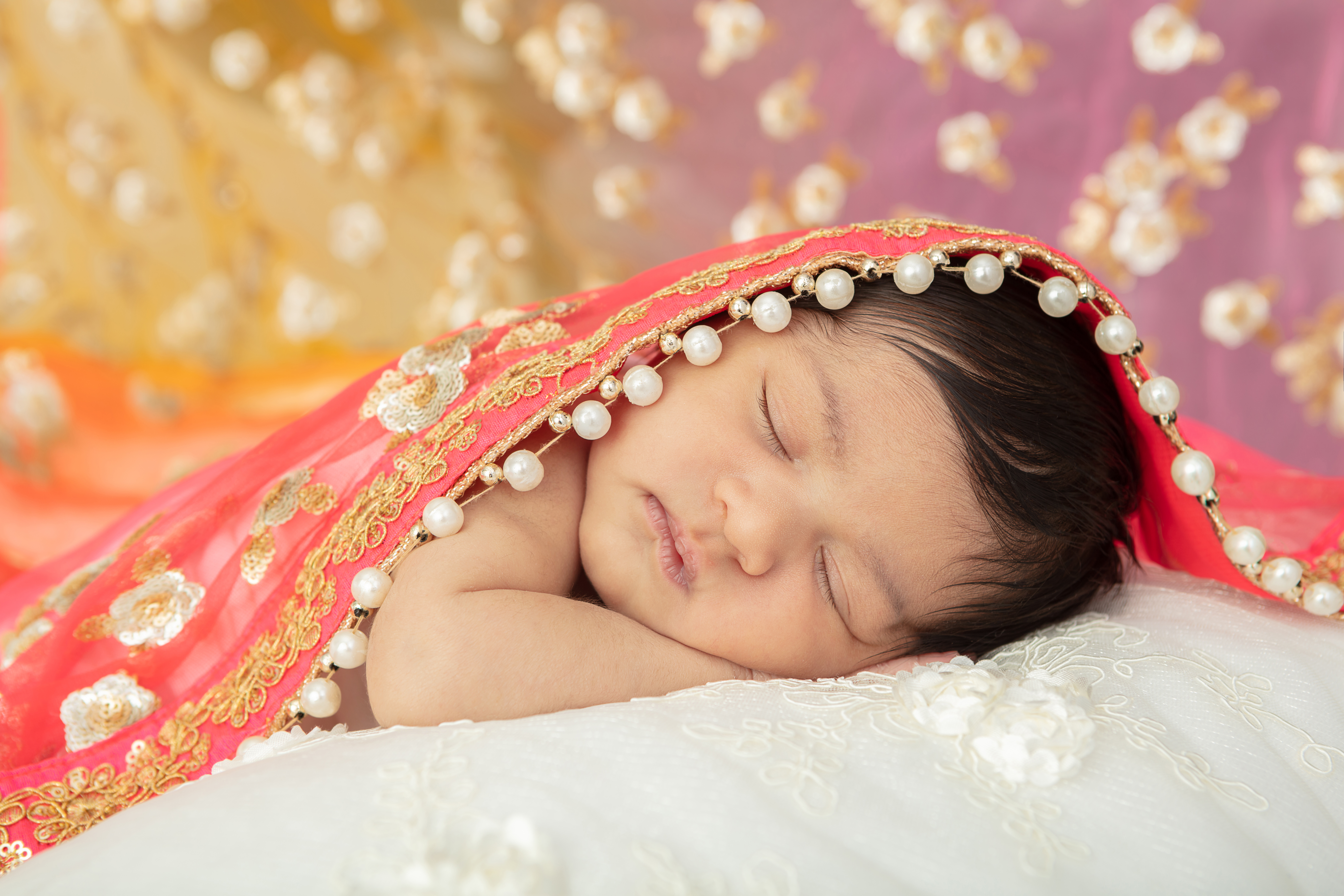 newborn Indian baby girl resting on a textured cream colored blanket, draped in her mother's sari
