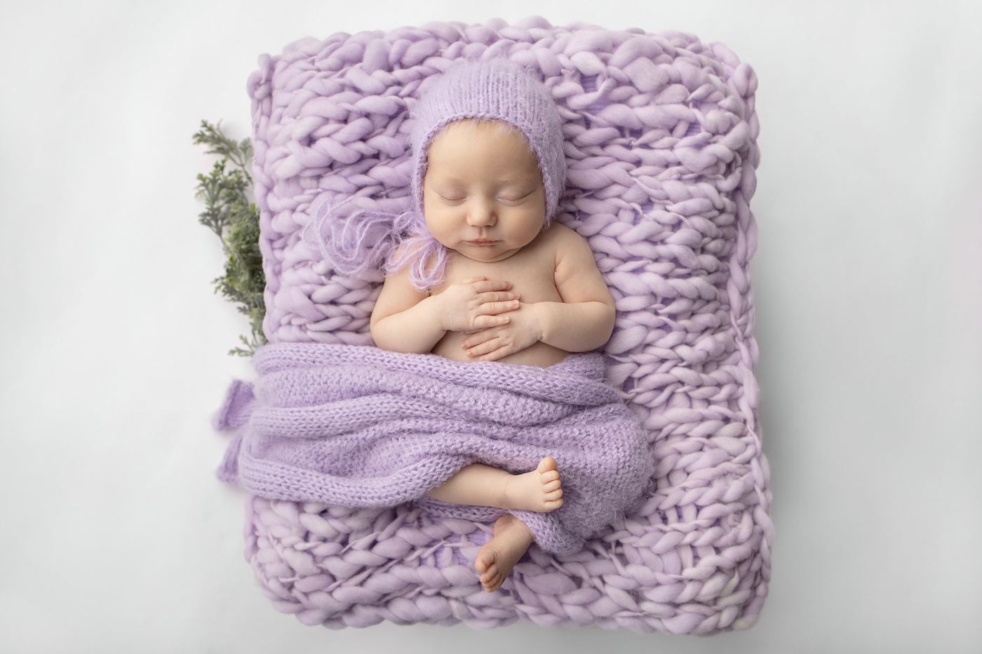 baby girl laying on a lavender chunky knit blanket