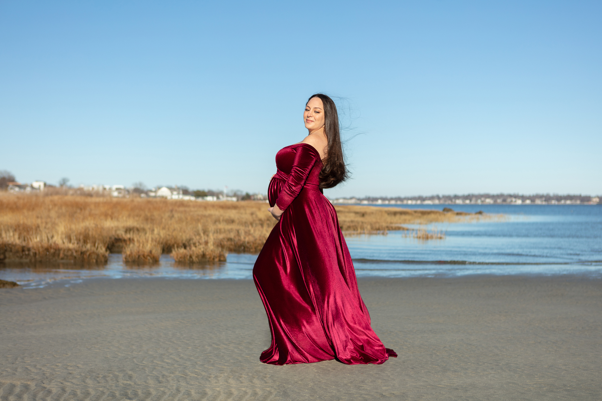 pregnant mama to be wearing a red velvet dress, standing on the beach at Tod's Point; Looking Up Photography