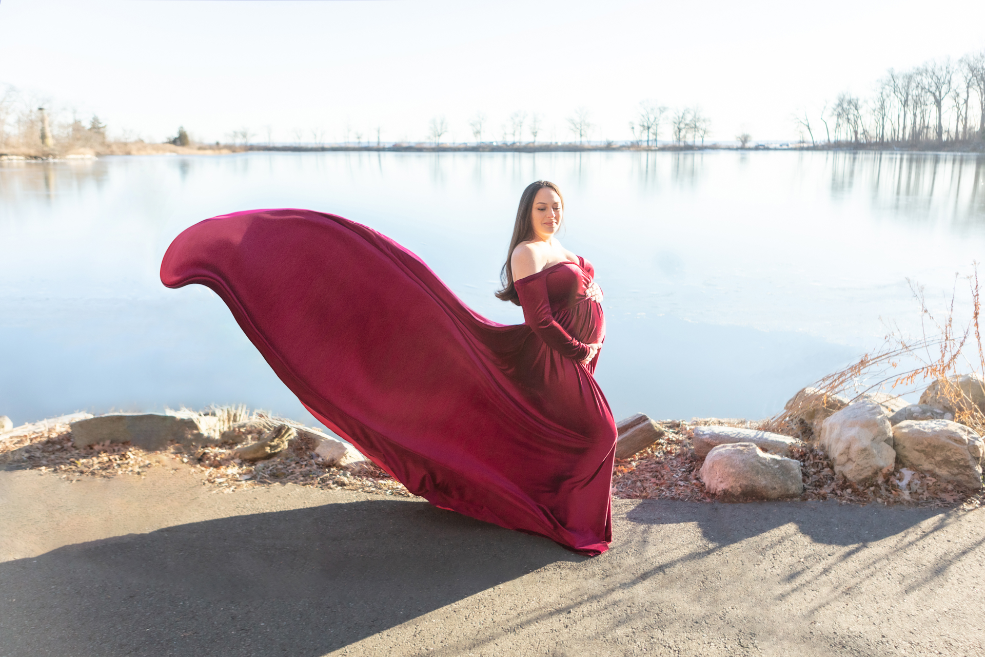Looking Up Photography; mother to be bright outdoor lighting with her gown flowing upwards behind her
