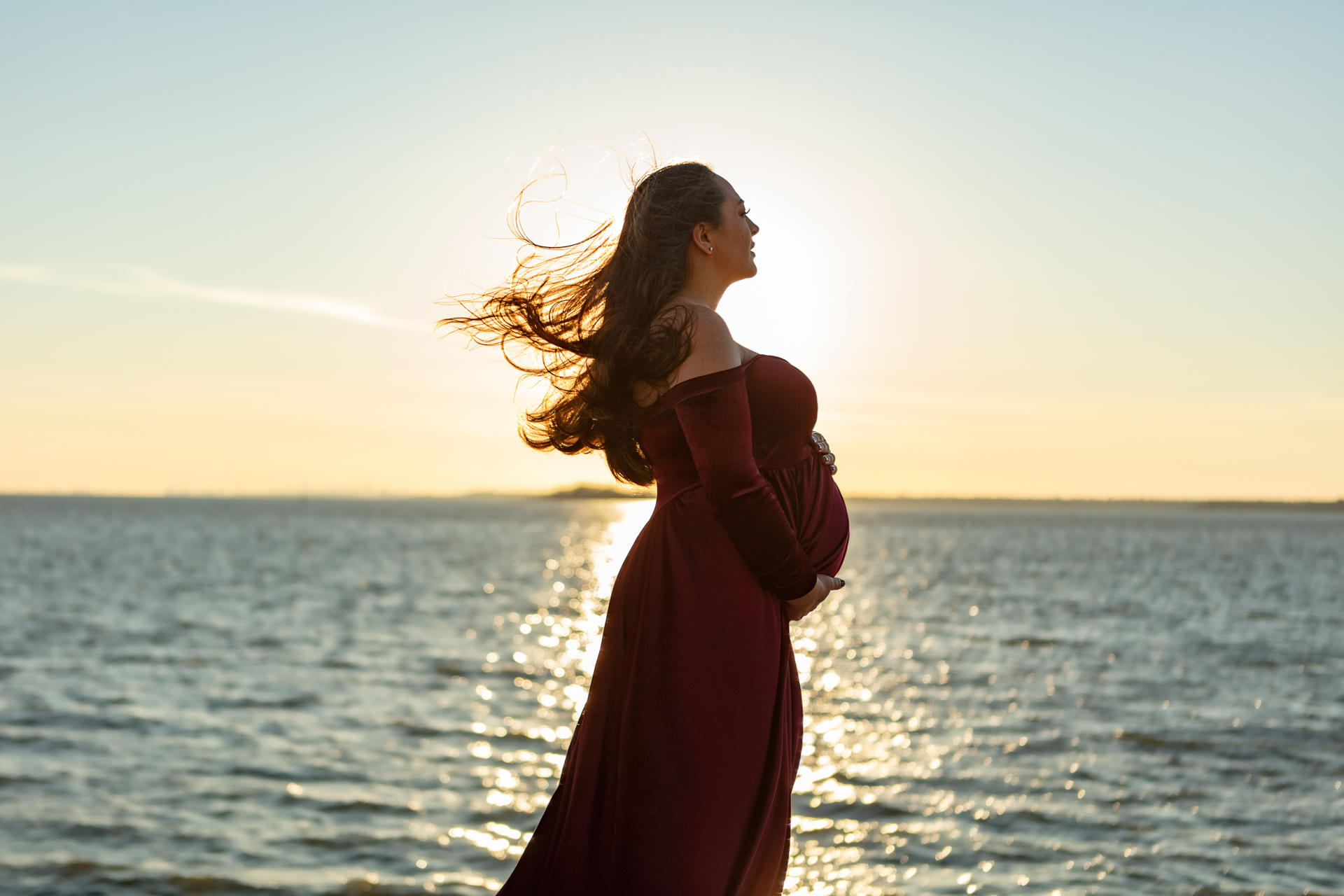 gorgeous golden hour photo of a pregnant mother to be looking out at the water; Looking Up Photography