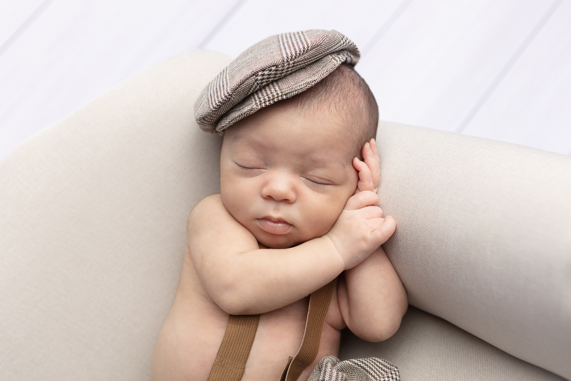 newborn baby boy with his hands folded under his head, wearing a plaid cap; CT baby photography