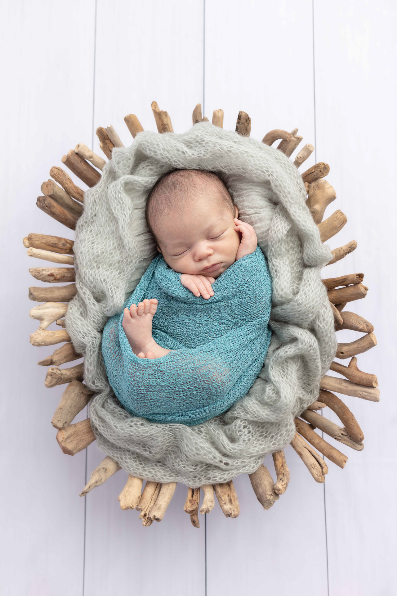 baby boy swaddled in an open knit blue swaddle, in a driftwood basket on a white wood floor; Looking Up Photography