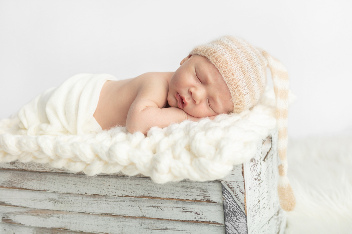 newborn baby boy asleep on his arms with his mouth slightly open; Karen Kahn